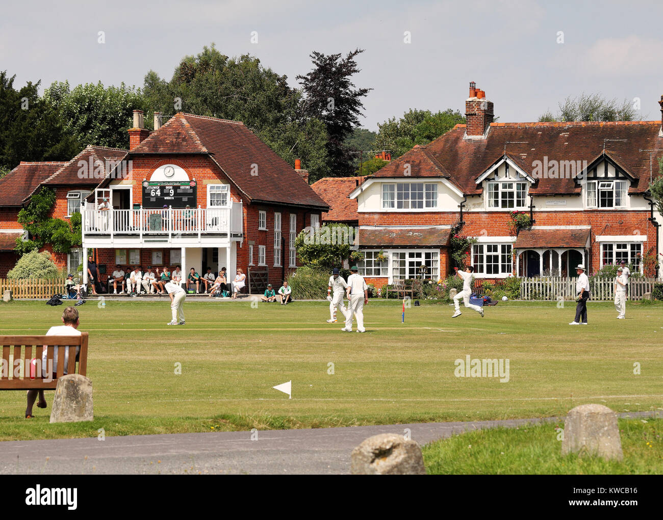 Bowler and fielders in action at an English Cricket match with pavilion and houses around the green - Stock Image