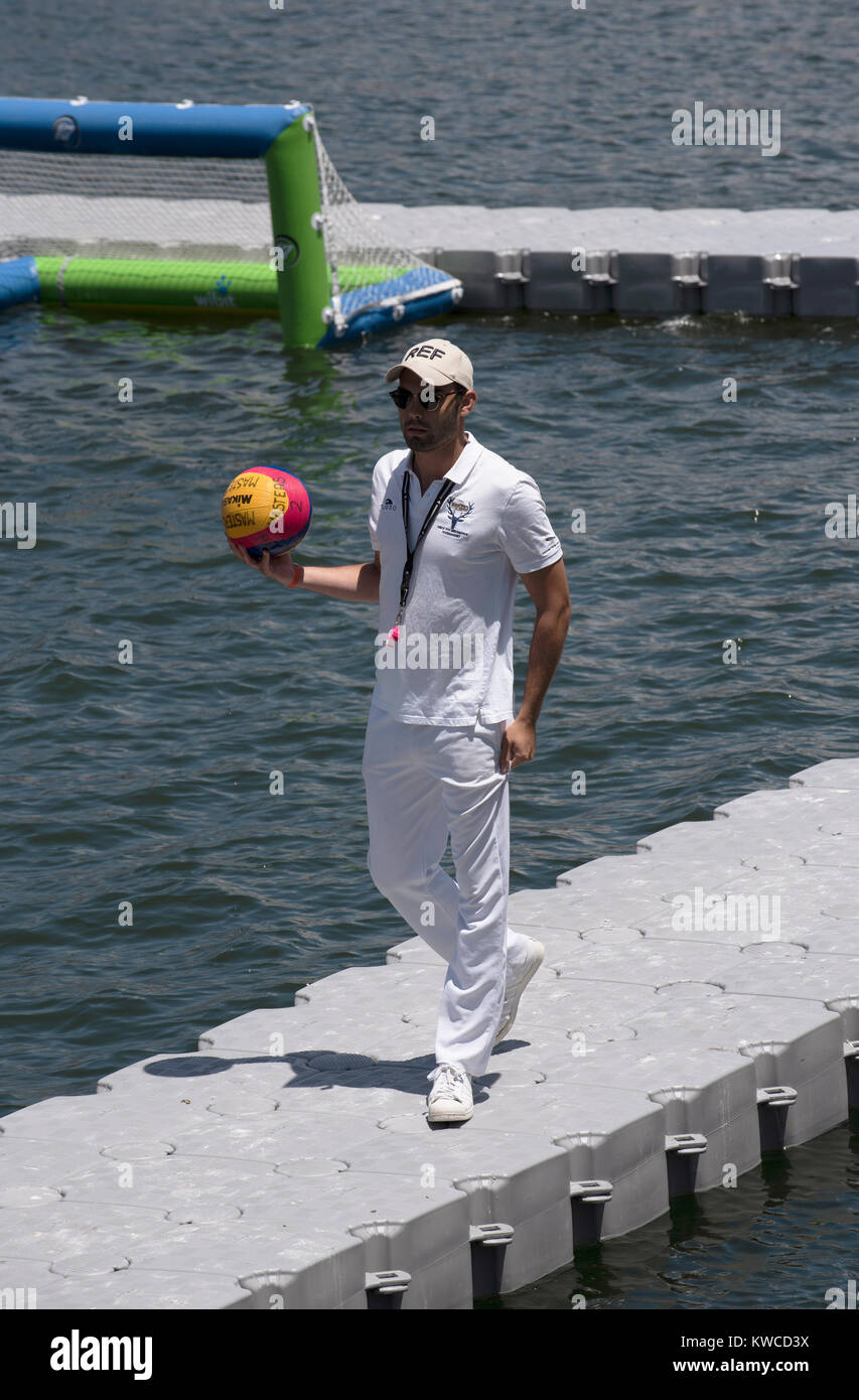 Waterpolo referee wearing white uniform and holding a ball on Cape Town Harbour, Western Cape, South Africa, December - Stock Image