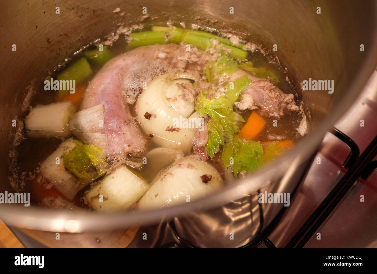 Turkey stock made from giblets and vegetables including onion carrot and celery simmering on gas hob in pot - Stock Image