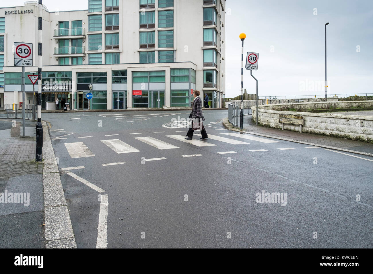 Newquay street scene - a woman walking across a zebra crossing in the quiet season in Newquay Town Centre. - Stock Image