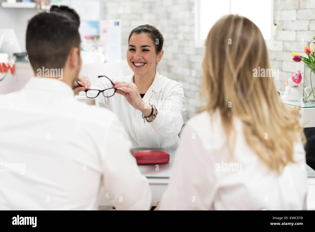 Young oculist woman selling glasses to couple at store - Stock Image