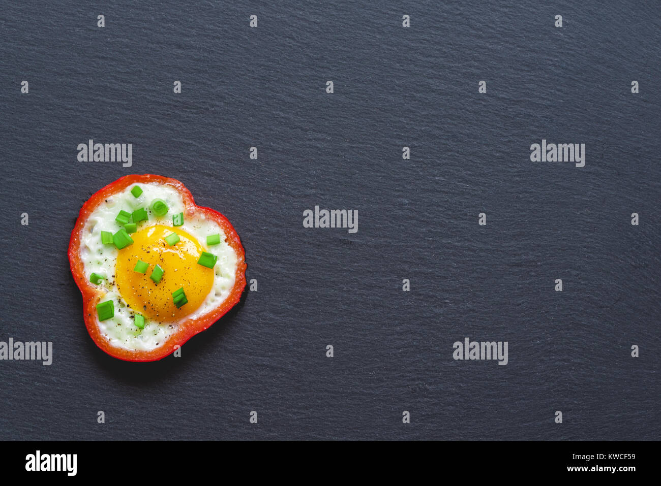 Fried eggs with red sweet pepper and chives on a black slate background. Top view. - Stock Image