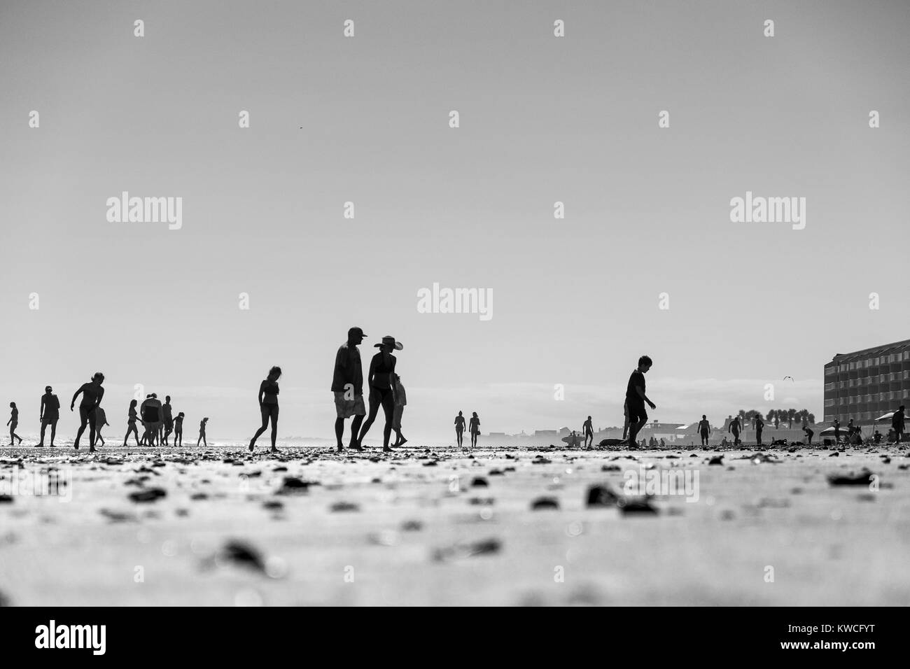 people in swimsuits walking on the beach on a hot summer day - Stock Image
