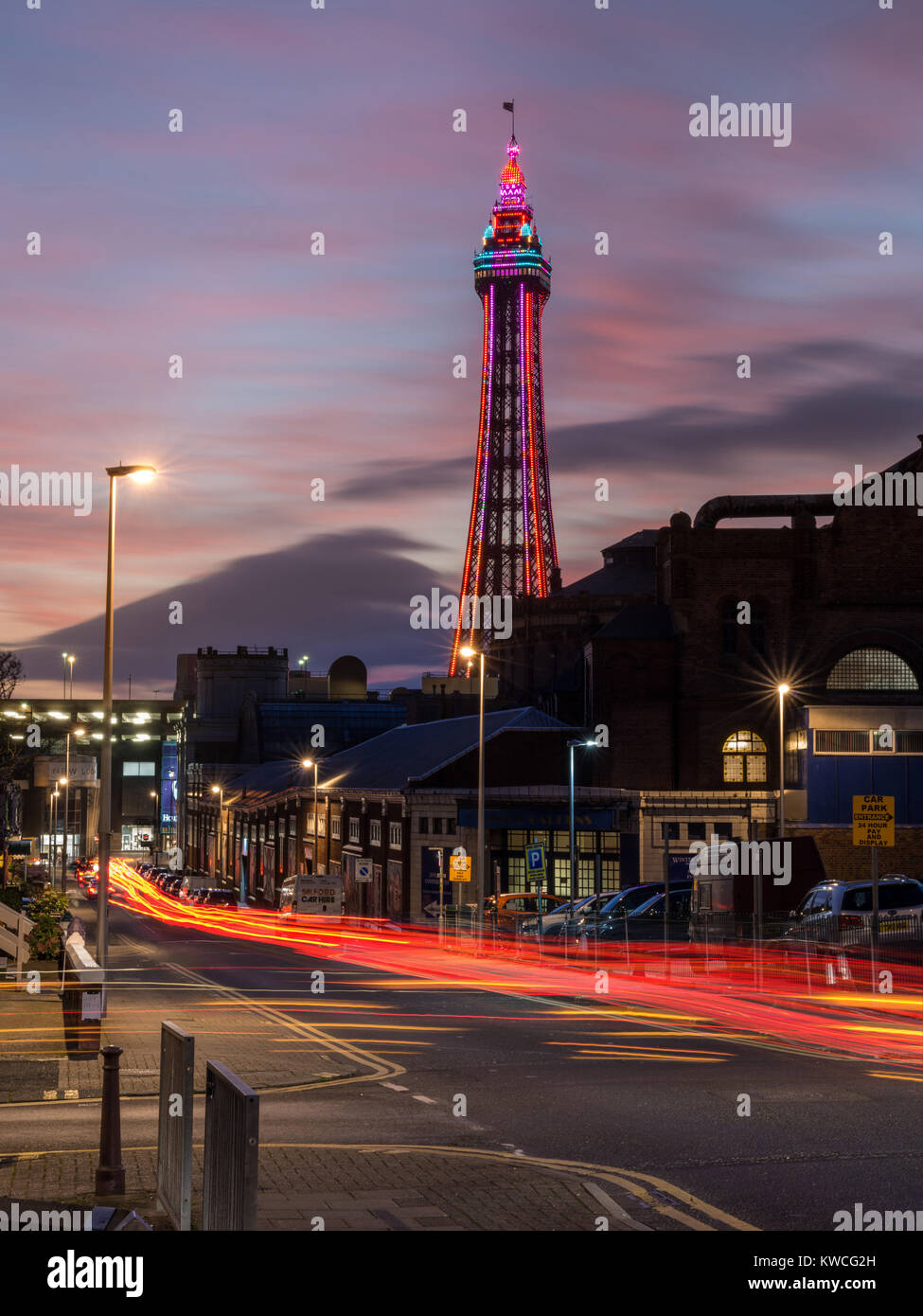 Blackpool Tower lit up at dusk with car light trails in foreground - Stock Image