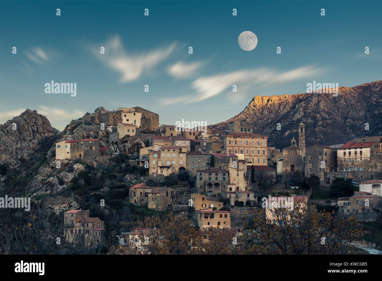 Full moon rising over the houses of the mountain village of Speloncato in the Balagne region of Corsica as the last - Stock Image