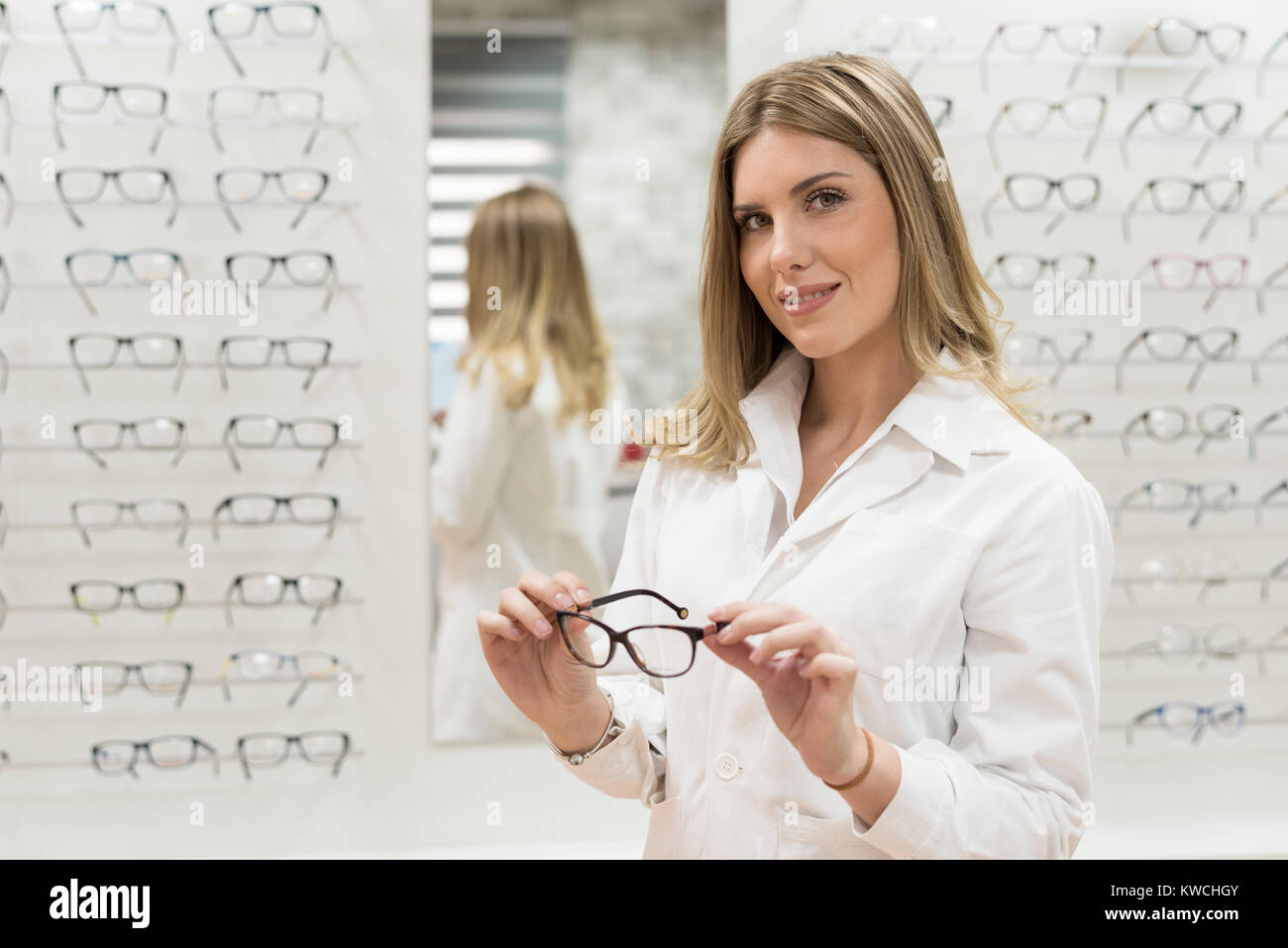Optometrist woman looking glassea at display in optical store with lab clothing - Stock Image