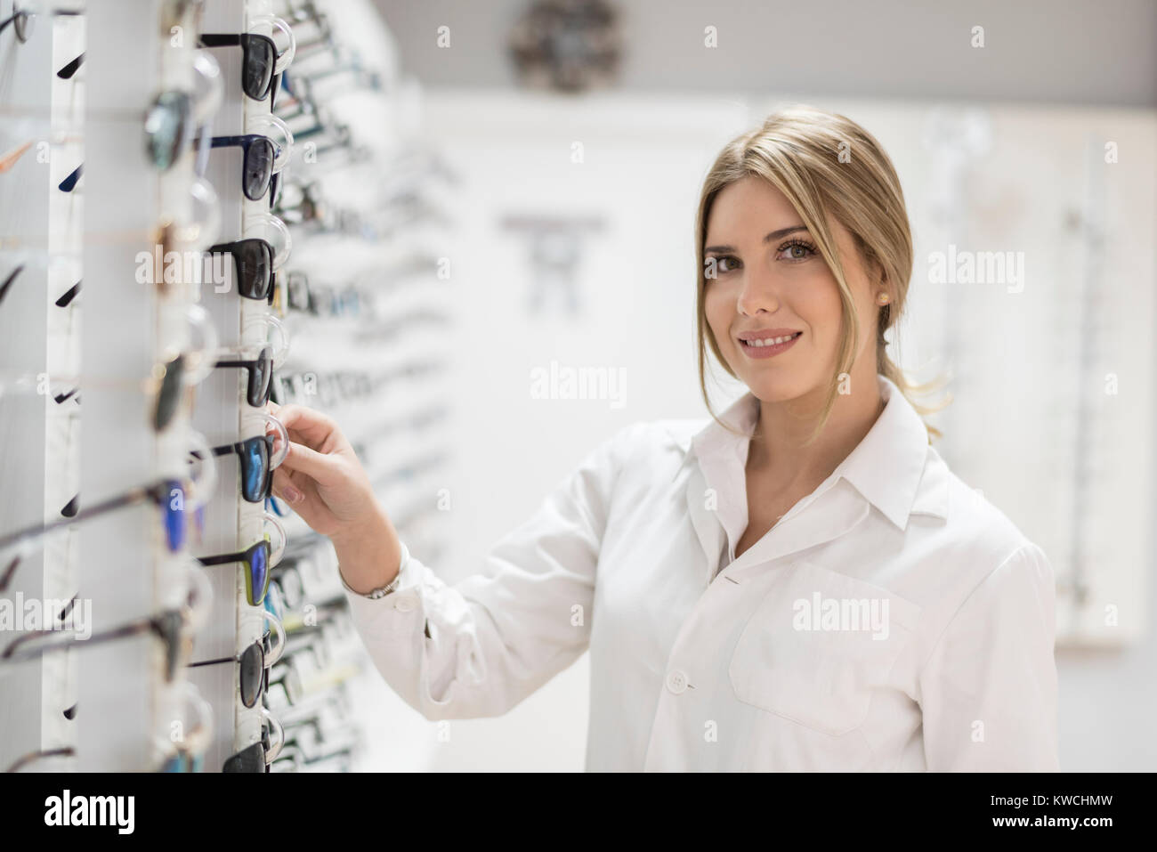Optometrist in eyeglasses store selecting lenses and looking at camera - Stock Image