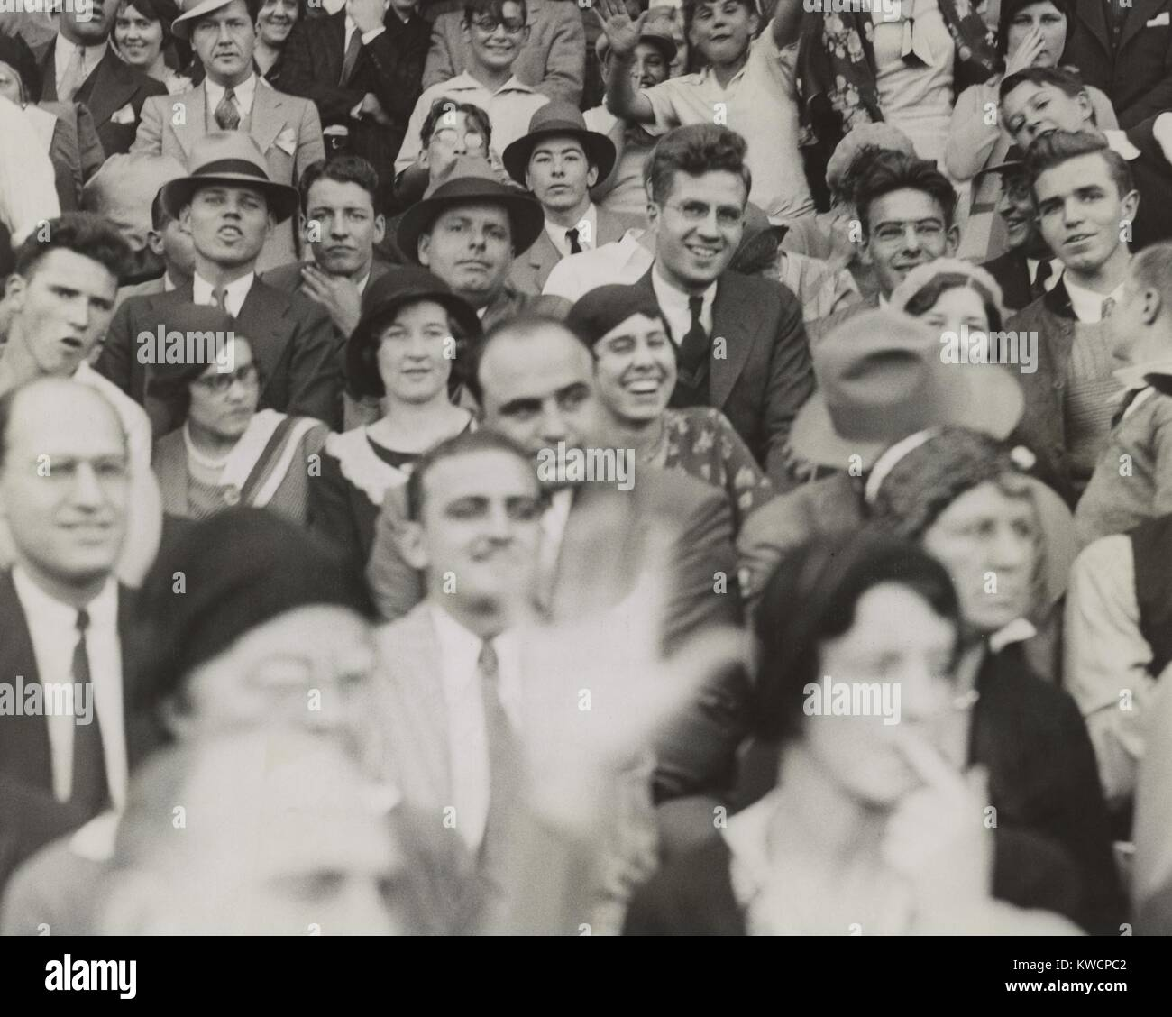 Al Capone (center), seated in front of three women, watching a college football game. He sits with other fans at Stock Photo