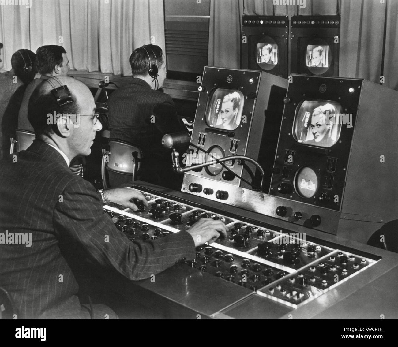 Television studio engineer gets several views of the image and use the complicated set of dials to control the tone - Stock Image