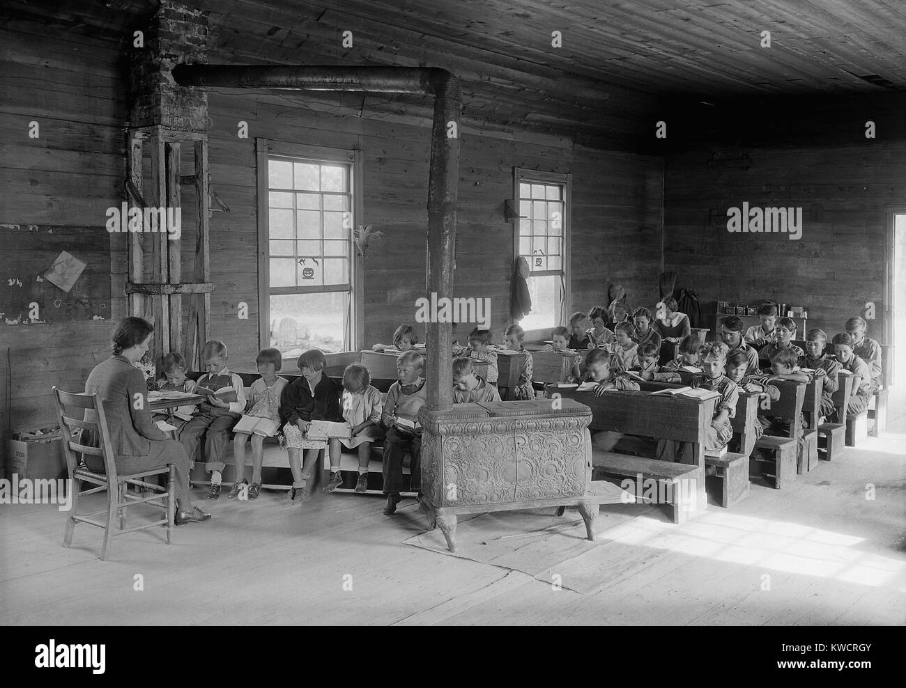 One room school with 28 students of various ages. Bare room lacks educational equipment and is heated by a wood - Stock Image