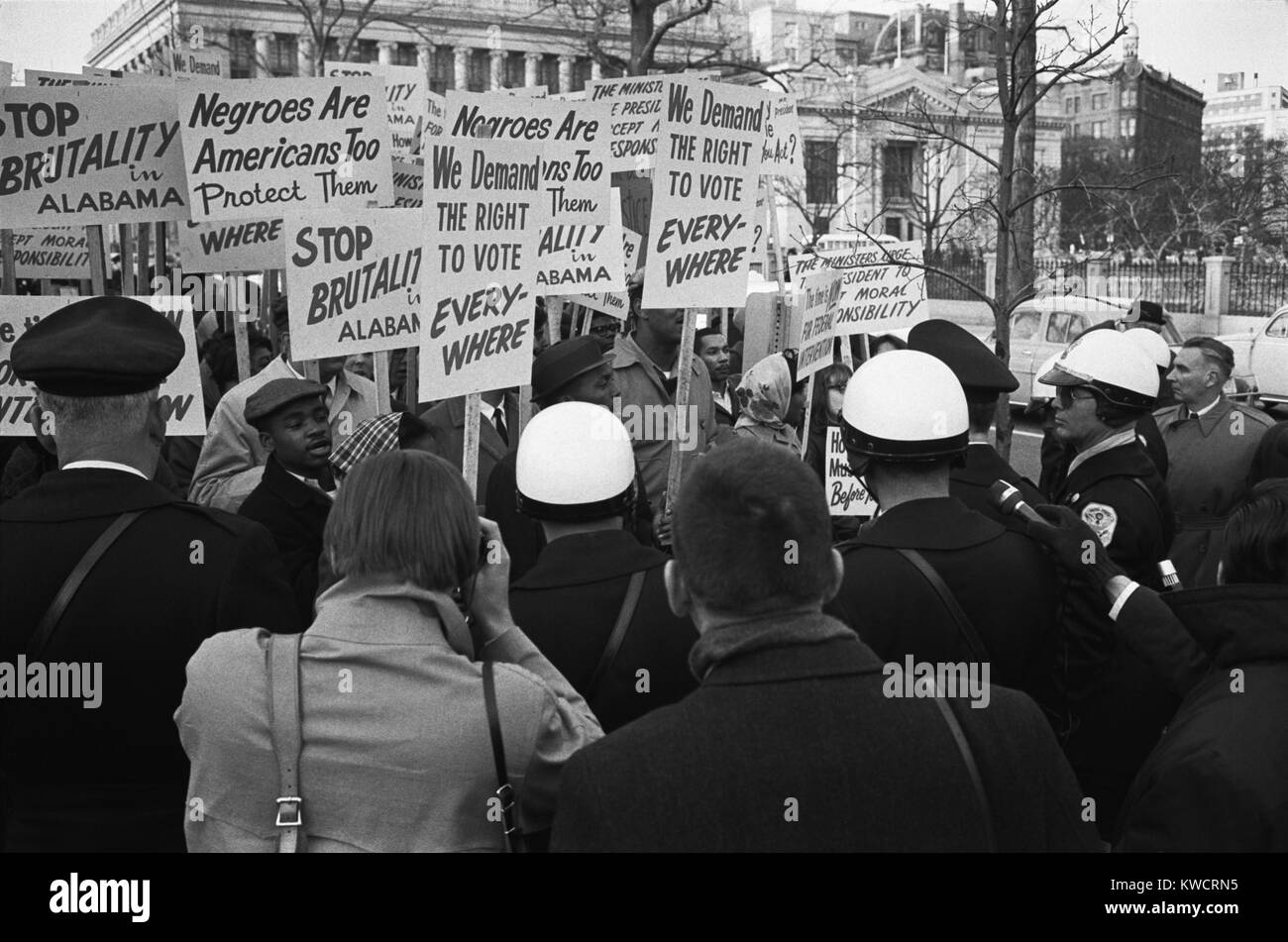 African Americans protesting outside the White House in support of Selma demonstrators. Their signs read, 'We demand Stock Photo
