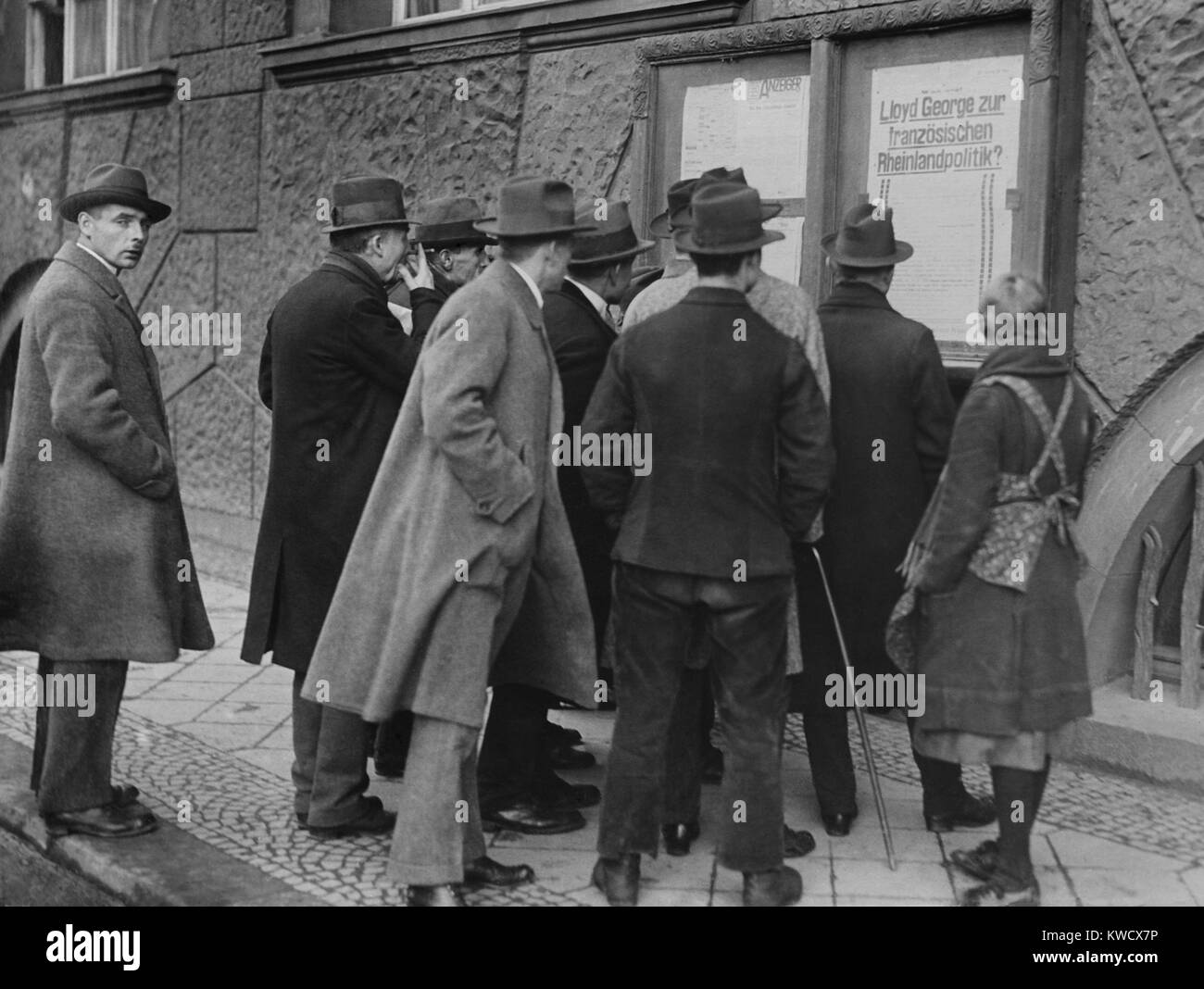 Germans reading broadside during the Franco-Belgian invasion of Essen, 1923. Poster reads that British Prime Minister - Stock Image