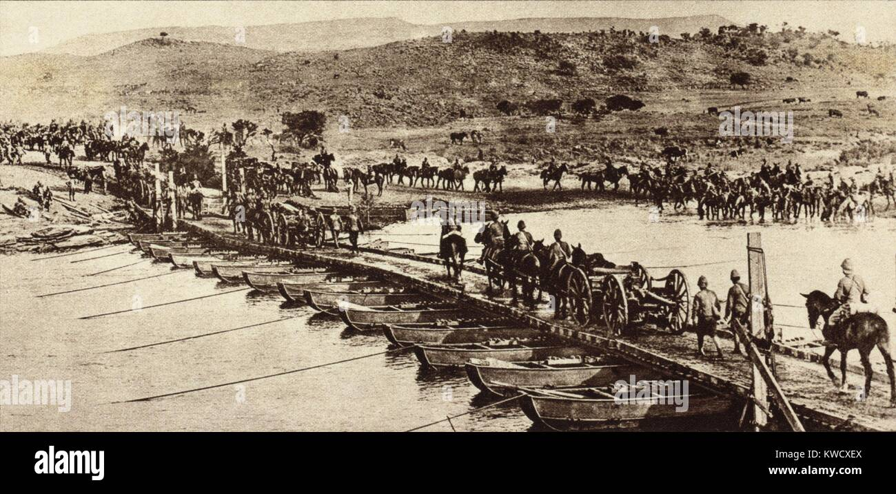 World War 1 in Africa. British Empire artillery crossing a pontoon bridge across a stream. At right the horses are - Stock Image