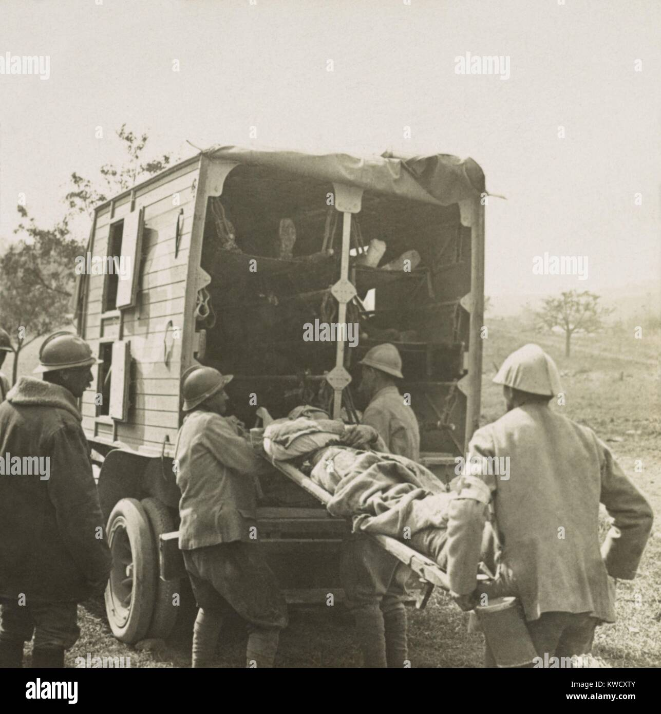 French soldiers load stretchers with wounded into motor ambulance for evacuation in World War 1. 1915-1918 (BSLOC - Stock Image
