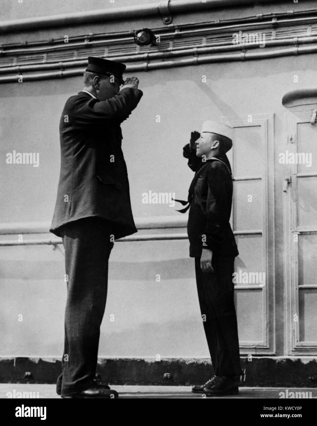 On the WW1 troop ship, USS Leviathan, the ships tallest and shortest sailor salute each other. The taller is the - Stock Image