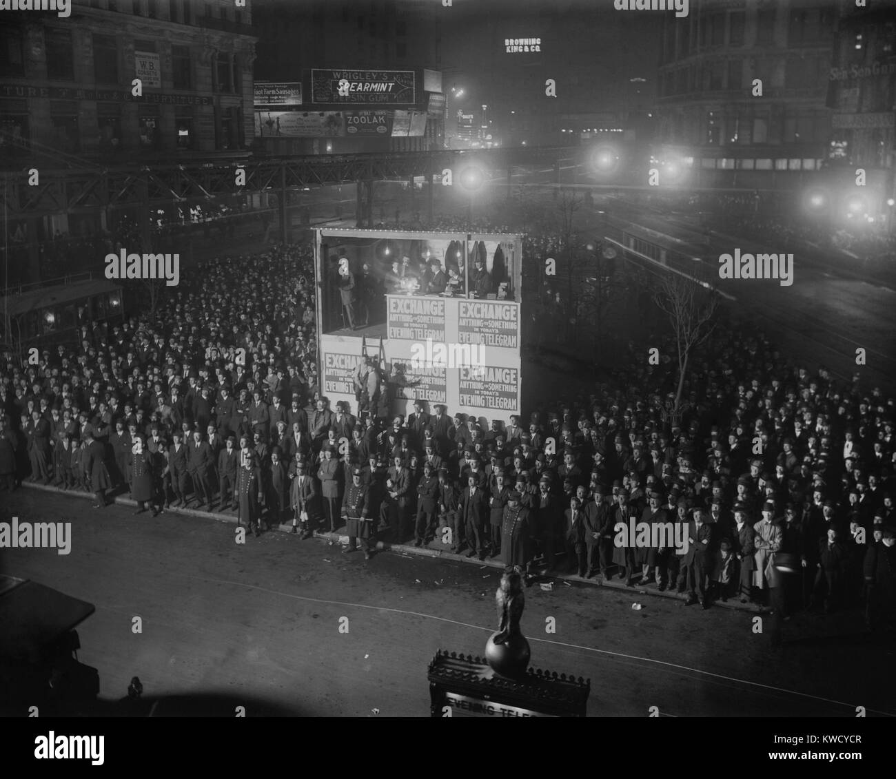 Election returns are projected from a booth by the New York Evening Telegram newspaper. A crowd has gathered to Stock Photo