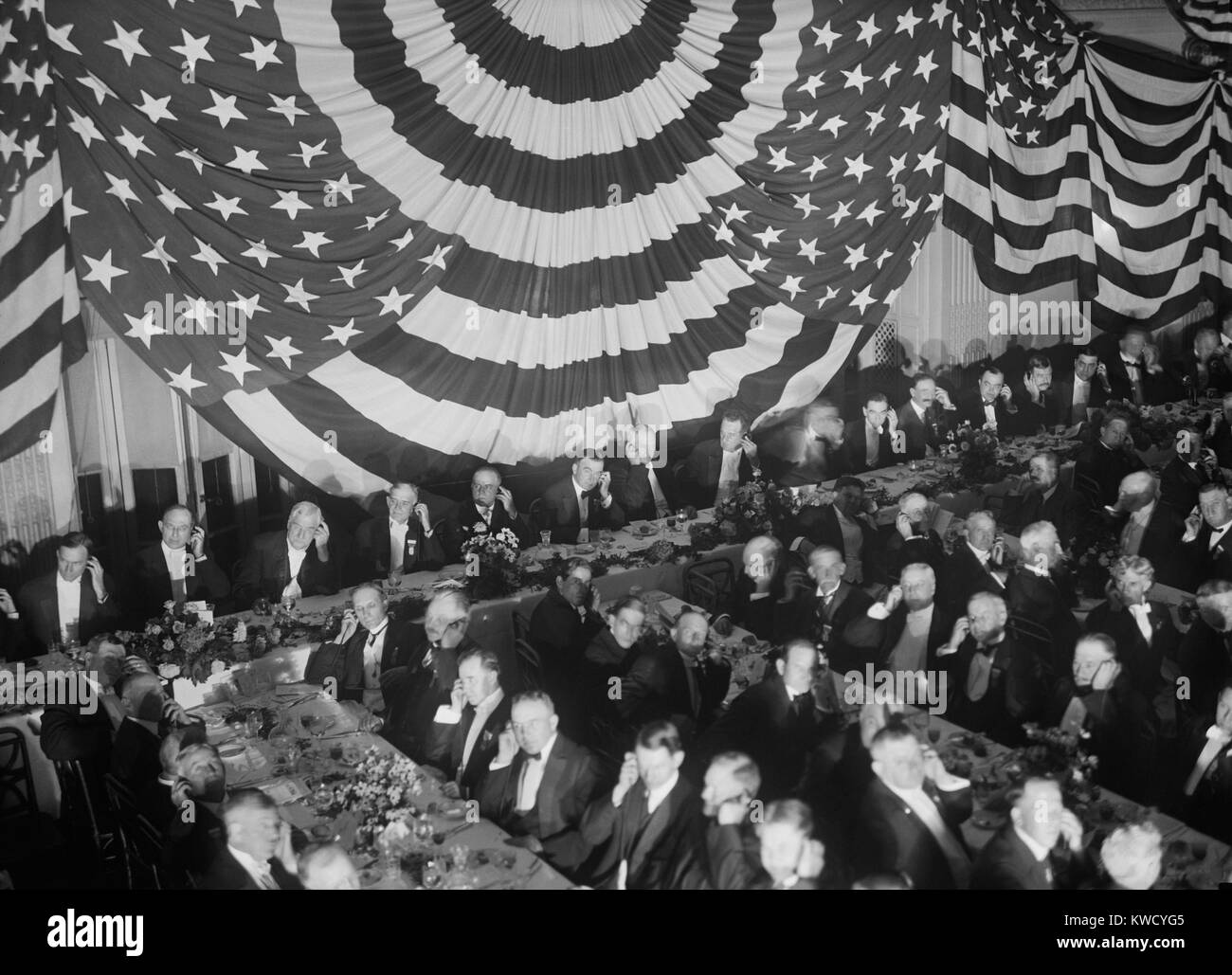 Banquet scene with seated men holding listening devices to their ears, Washington D.C. In 1915 loud speakers were Stock Photo