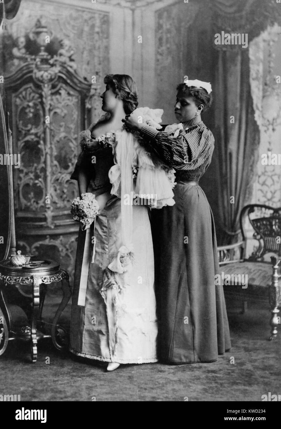 African American ladys maid helps a wealthy woman get dressed in luxurious evening gown, 1897.  (BSLOC_2017_20_111) - Stock Image