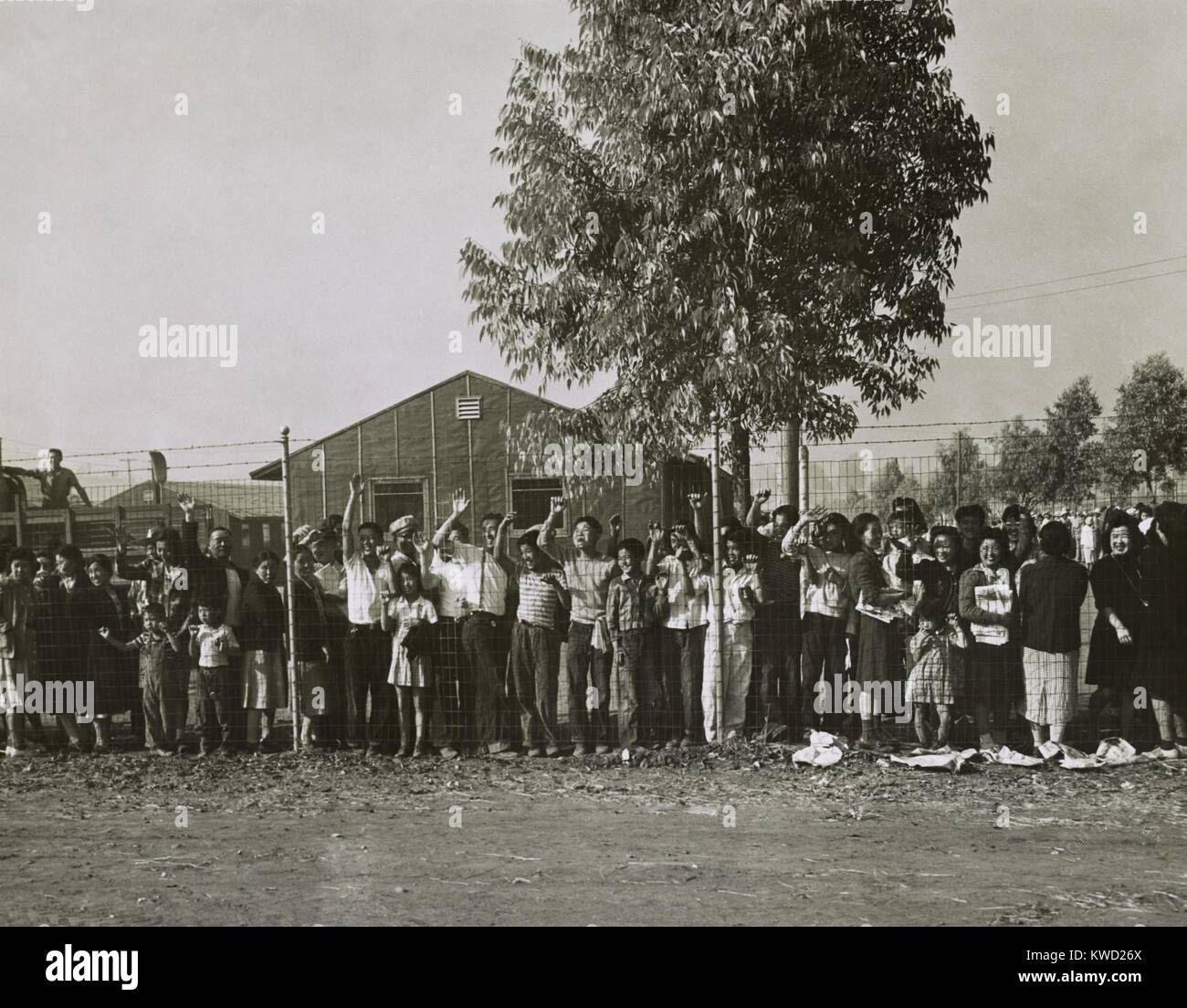 Japanese Americans internees waving farewell from behind a wire fence at Pomona, CA, 1942. Men, women, and children - Stock Image