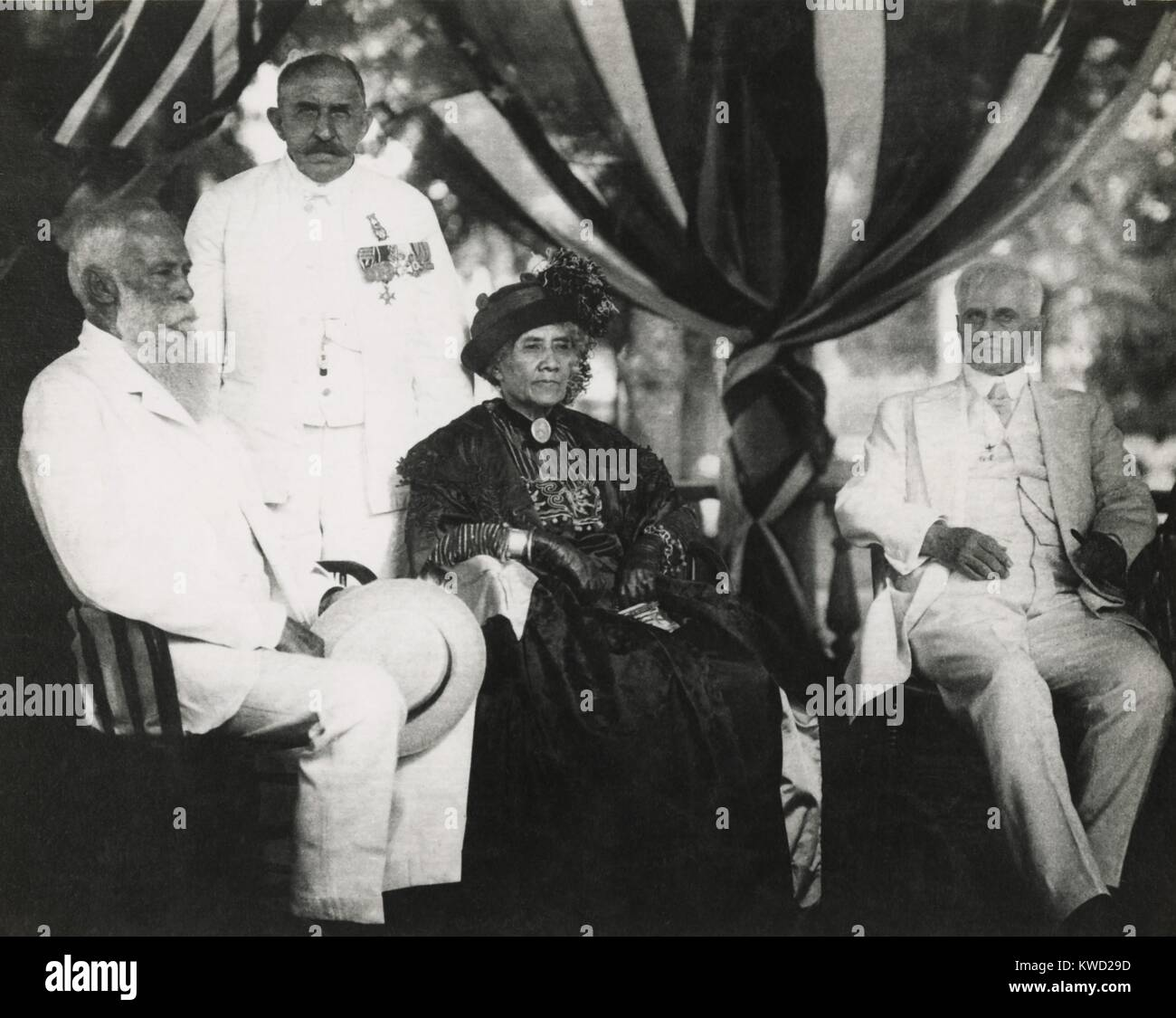 Ex-Queen Liliuokalani on her 70th birthday, seated with Sanford Dole (left) in 1914. At right is Lucius Eugene Pinkham, Stock Photo