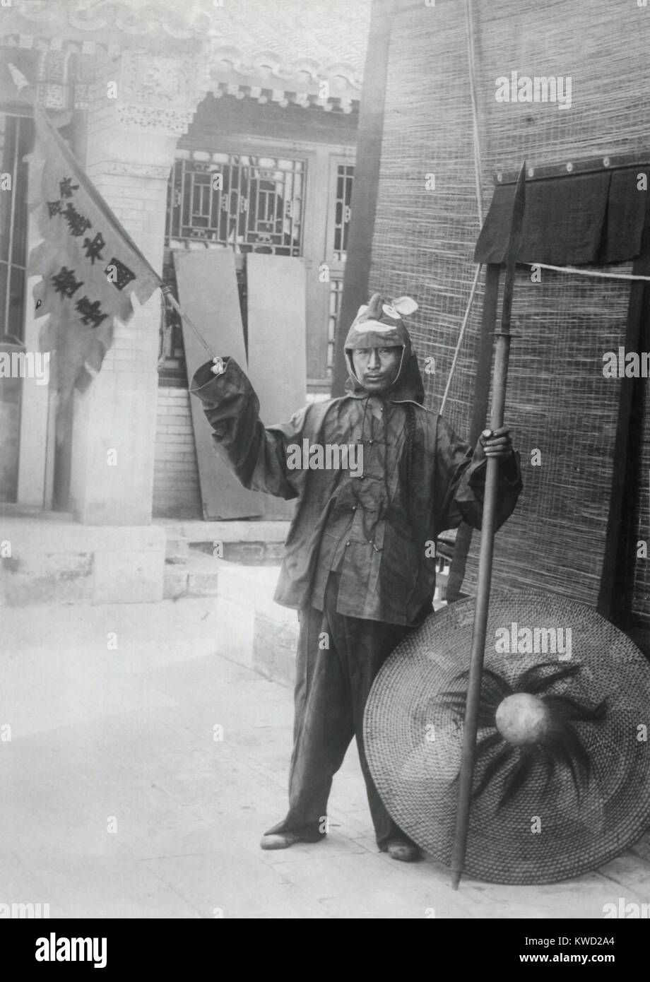 Chinese Boxer with shield and banner on urban street, c. 1900. The Boxers, were called by the Chinese, 'Ih-hwo-Ch'uan, - Stock Image