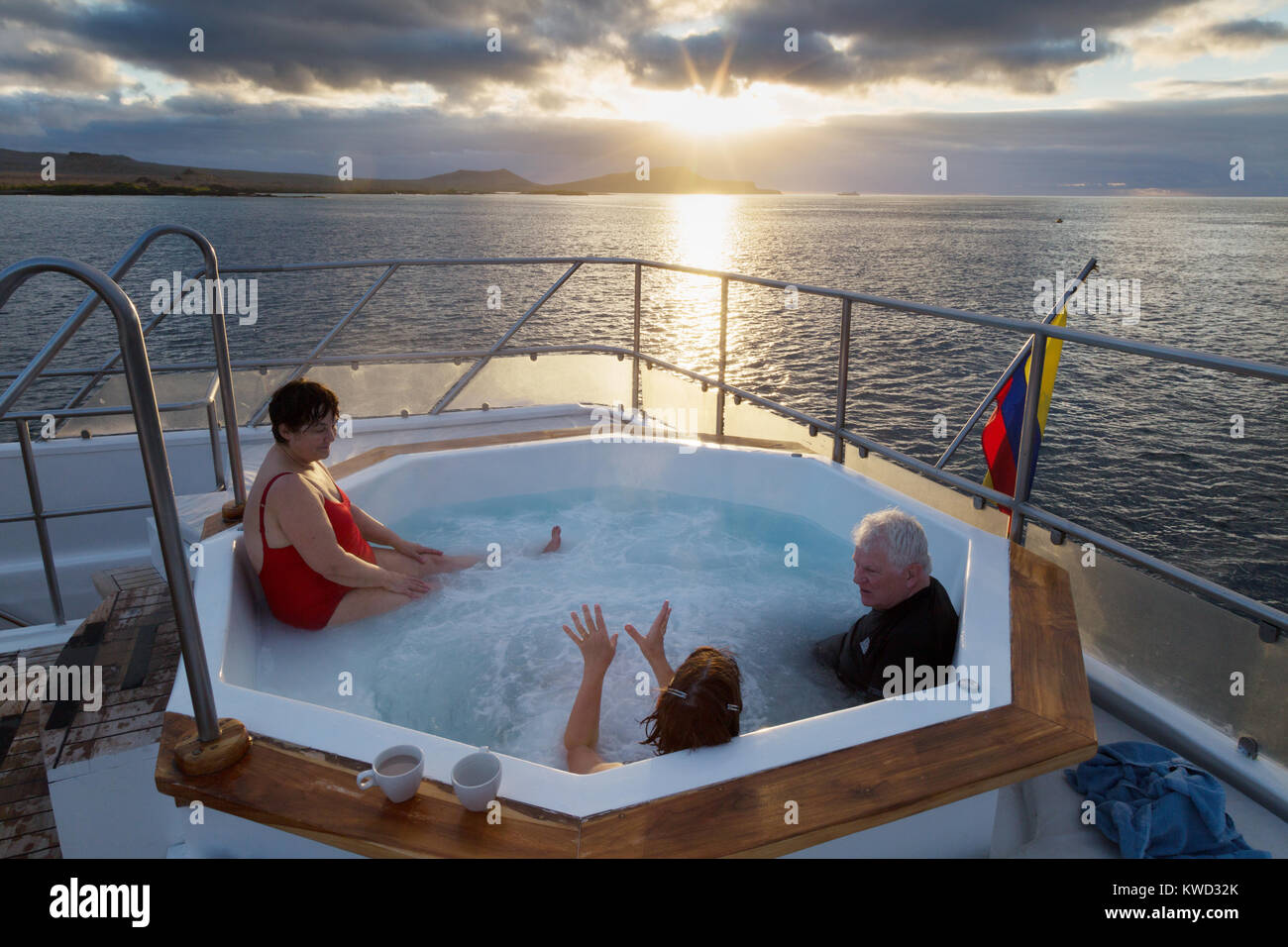 Galapagos travel - tourists in a jacuzzi on their cruise ship watching sunset over Floreana Island, Galapagos Islands, - Stock Image