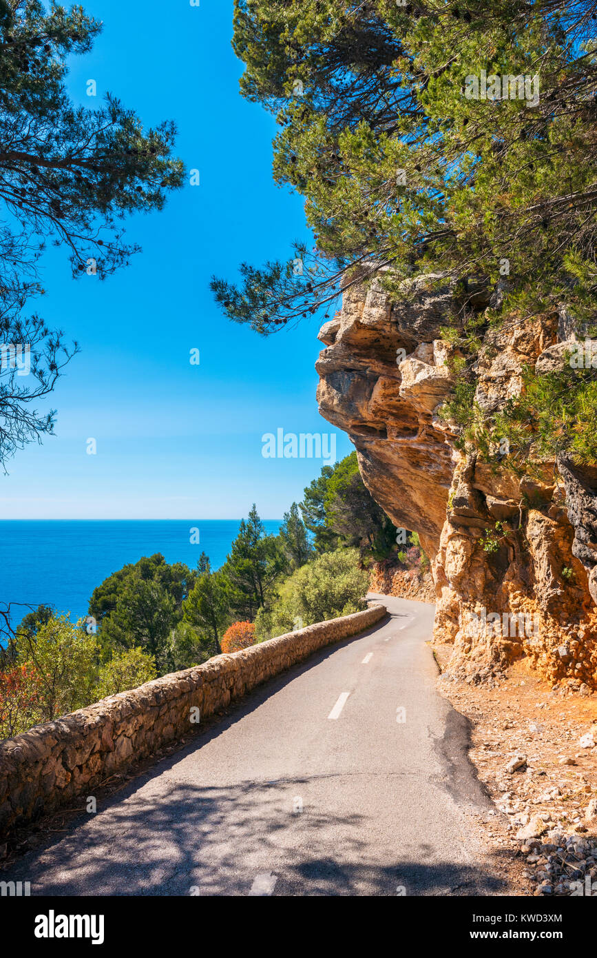 Narrow Coastal Road with Overhanging Rock in Mallorca Spain - Stock Image