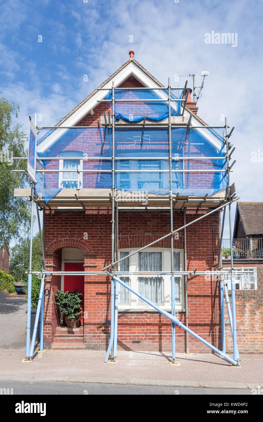 House being renovated and covered with scaffolding, High Street, Hurstpierpoint, West Sussex, England, United Kingdom Stock Photo