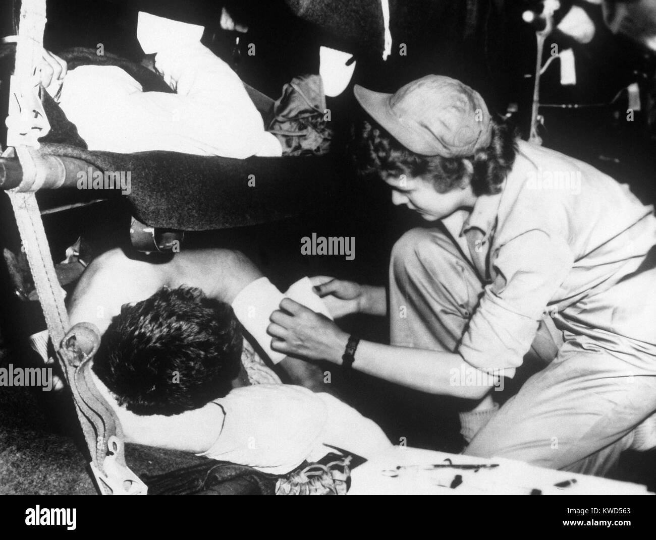 U.S. flight nurse dresses a soldier's wound during the flight from Korea to Japan, May 1951. Korean War, 1950 - Stock Image