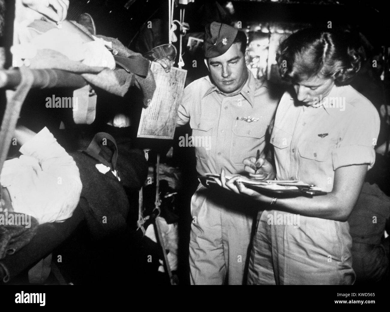 U.S. flight nurse checks patient records with C-54 aircraft commander Maj. George Cichy, October 1952. Korean War, - Stock Image