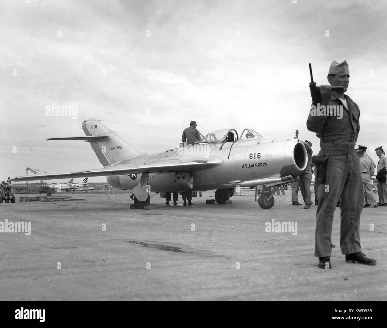 Soviet MiG-15 jet fighter delivered by defecting North Korean pilot Lt. No Kum-Sok in 1953. Its guard is armed with - Stock Image