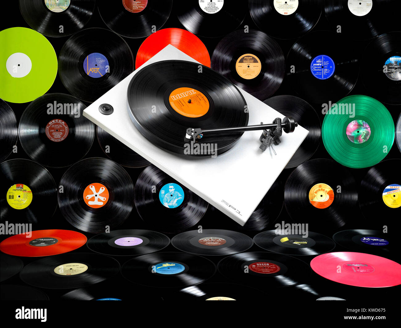 A floating record player in front of a wall of old vinyl records - Stock Image
