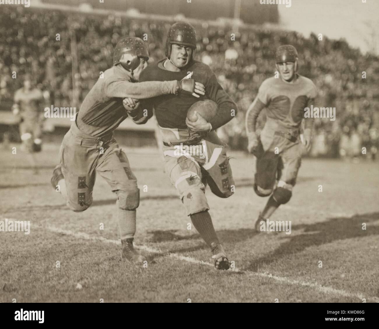 1920s football action. Hundreds of spectators watch from stadium seats. (BSLOC_2015_17_124) - Stock Image
