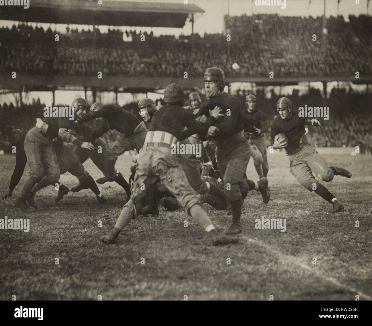 1920s football action. Thousands of spectators watch from double decker stadium seats. (BSLOC_2015_17_125) - Stock Image