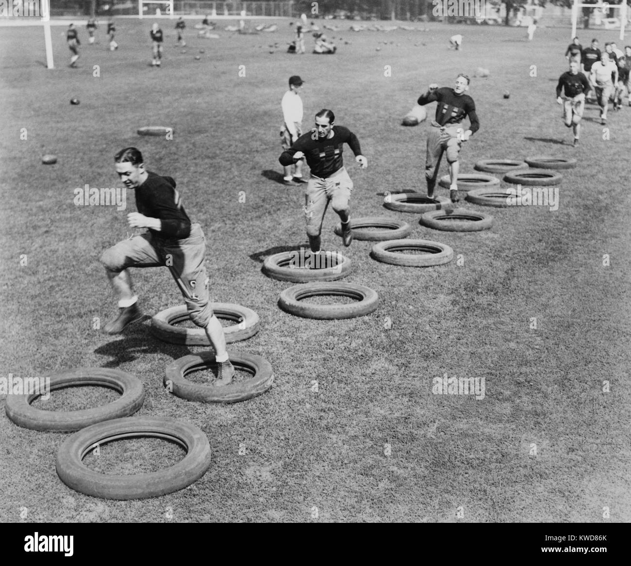 West Point's football squad high stepping through a maze of tires during their first practice. 1920s. (BSLOC - Stock Image
