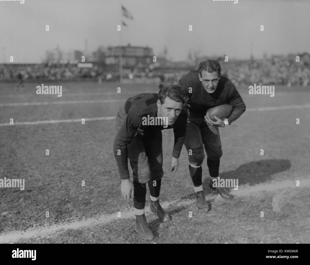Harold 'Red' Grange (right) and his brother Garland Grange on football field. In the distance are spectators - Stock Image