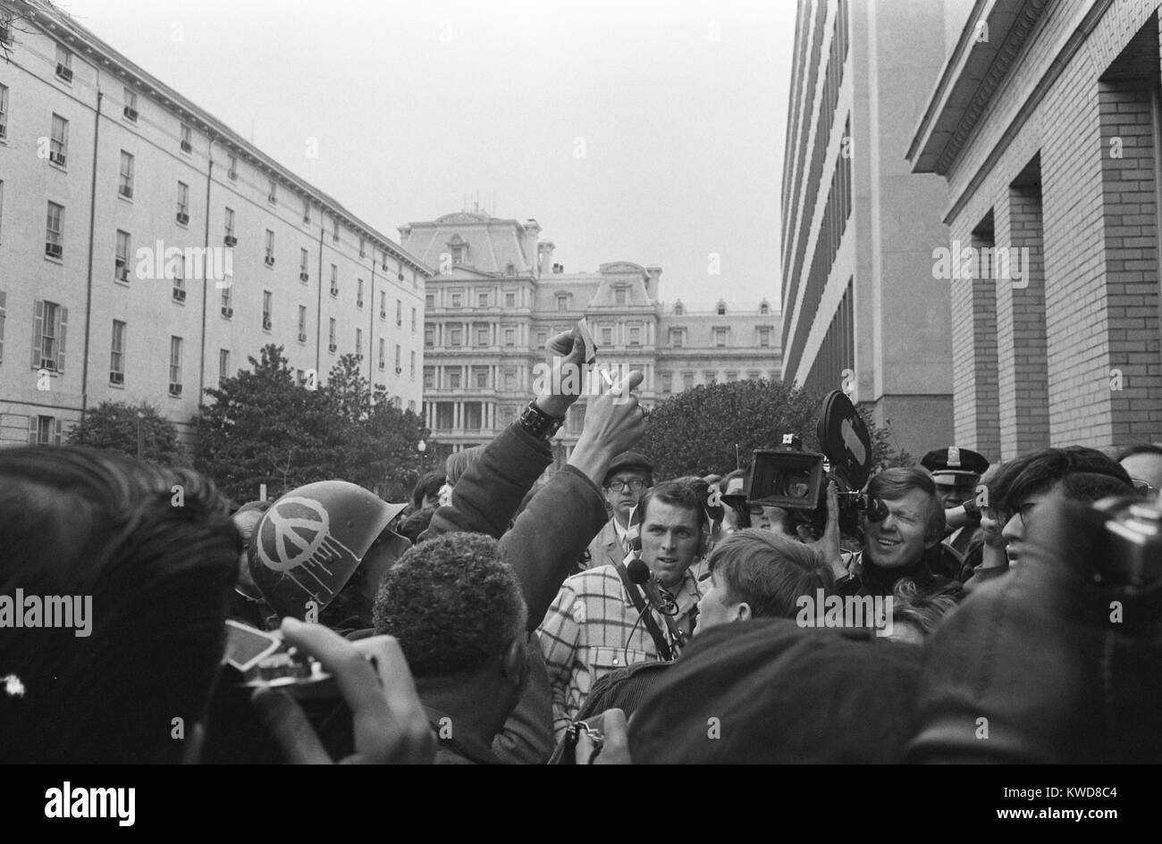 Young American man wearing a helmet with a peace sign burning his draft card, March 19, 1970. He was demonstrating - Stock Image