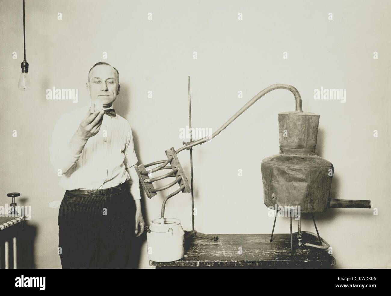 Moonshine still recently confiscated by the Internal Revenue Bureau. An employee holds a glass of alcohol distilled - Stock Image