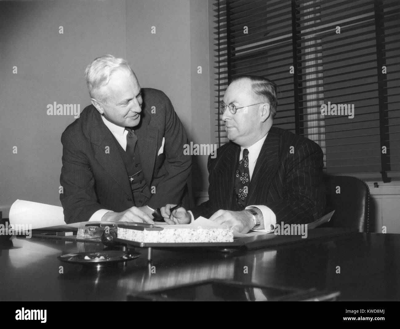 War Production Board leaders oversaw industrial planning in WW2. Production Division Director W. H. Harrison (left), - Stock Image