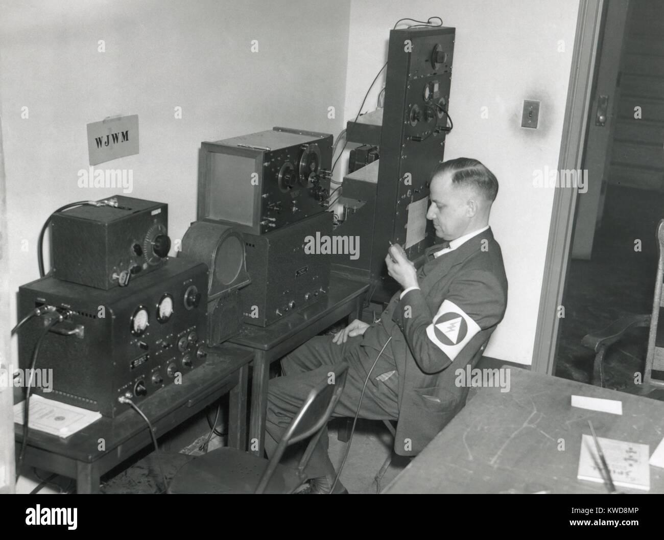 World War 2 civil defense worker monitors three War Emergency Radio Service transmitter-receivers. Tuned to different - Stock Image
