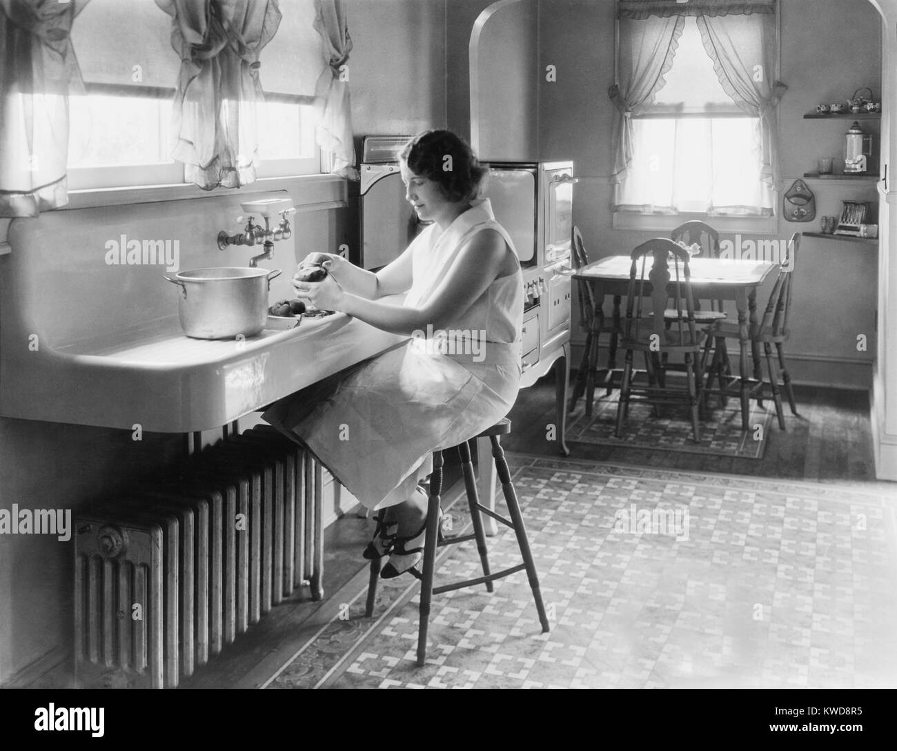 woman seated on stool peeling potatoes in modern kitchen c 1925 - 1920s Kitchen