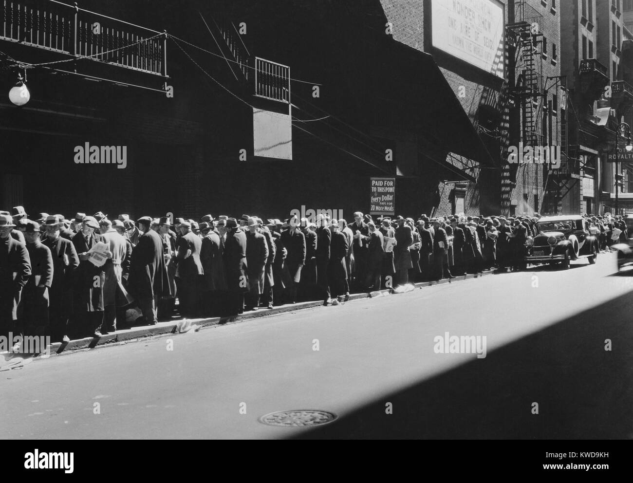 New York men in a bread line during the Great Depression, 1935-38. The sign read, 'Paid Up to this Point, Every - Stock Image