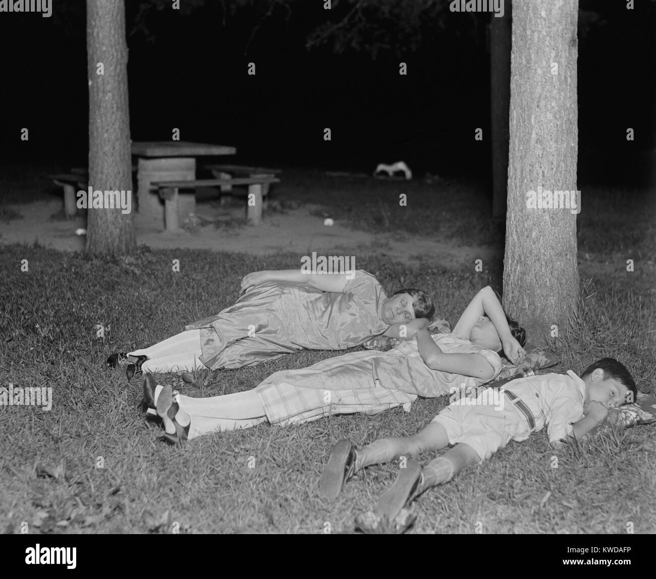 Escaping stuffy apartments during nighttime summer heat in Rock Creek Park, 1926. Two women and a boy rest on the - Stock Image