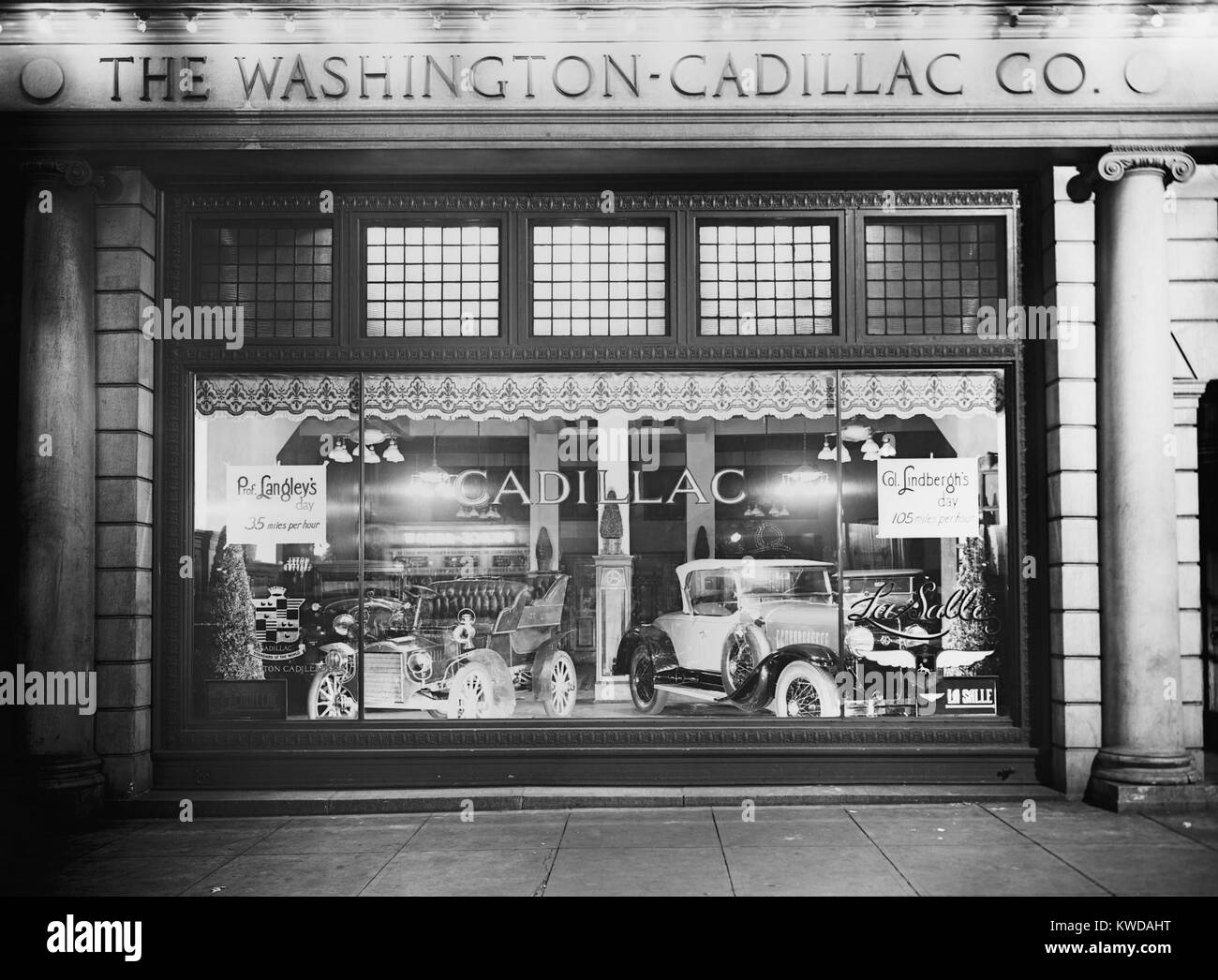 1927 Cadillac LaSalle (right) shares the showroom window with a vintage model. The Washington, D.C. dealership window - Stock Image