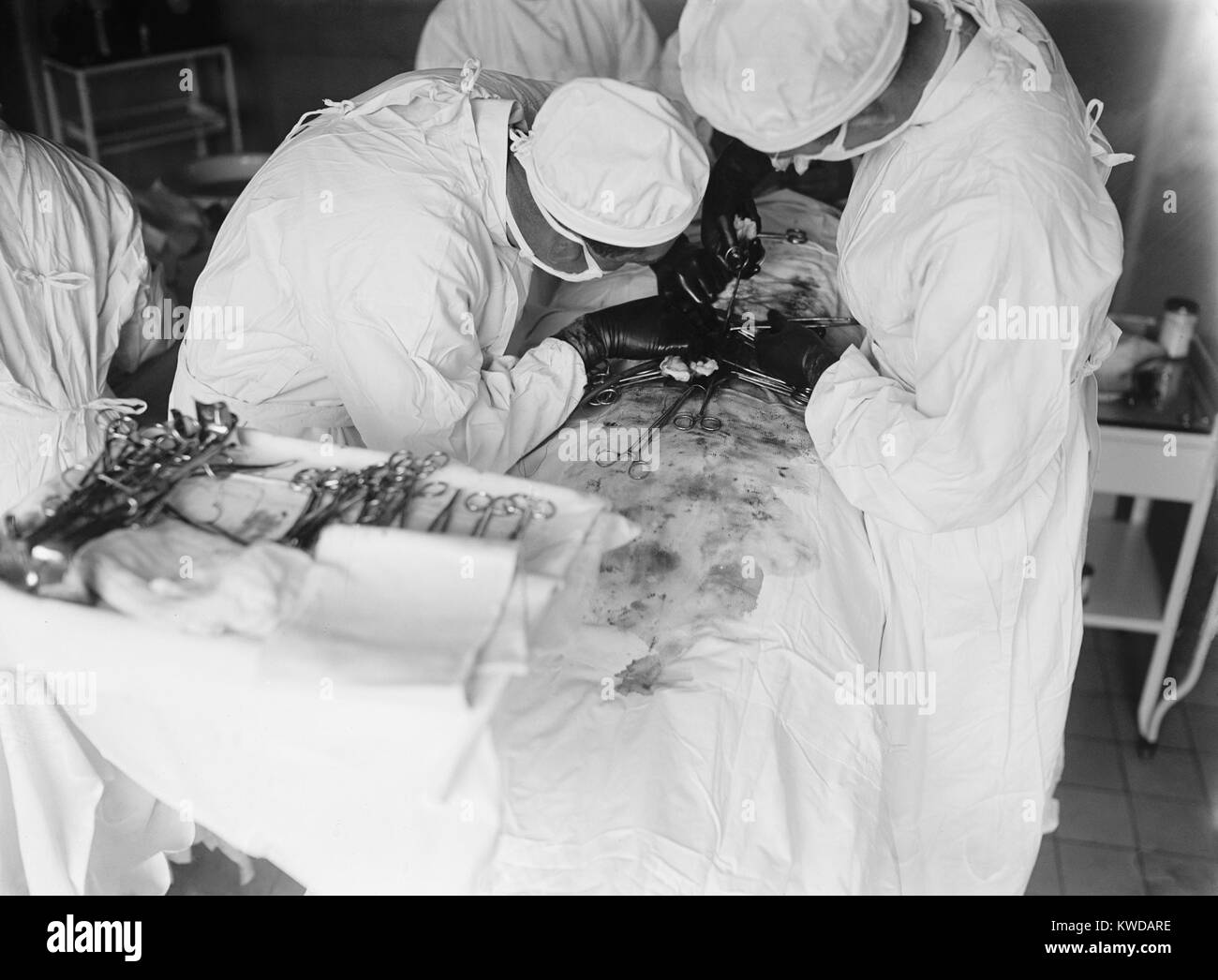 Attending surgeon leans over to work closely over a patient's abdomen. The surgical field is stained with blood. Stock Photo