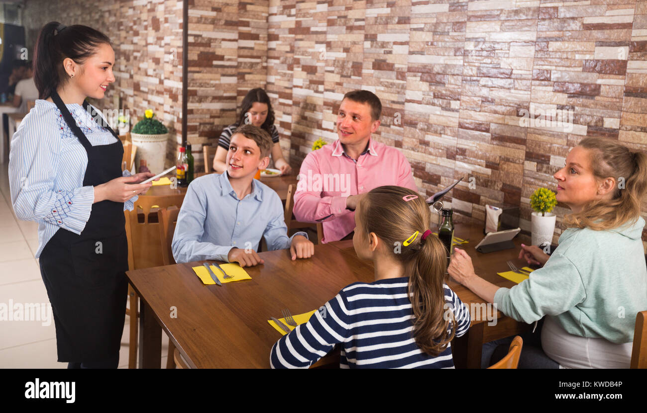 Family are giving order to cheerful waitress in comfy cafe. - Stock Image