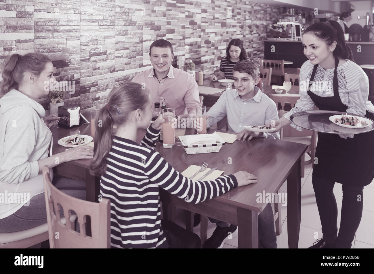 Young brunette waitress serving cheerful family in comfy family cafe - Stock Image