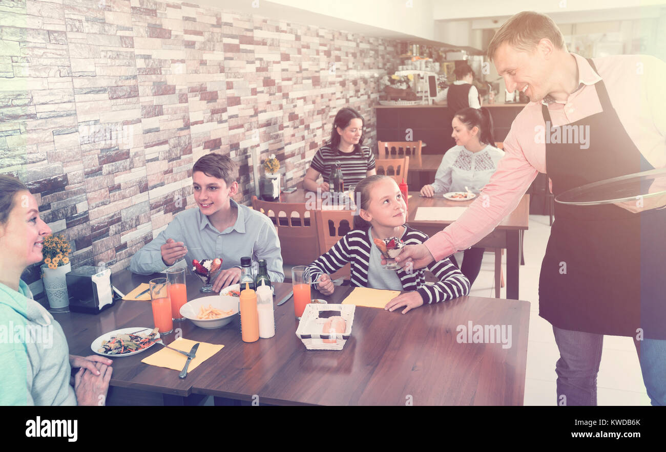 male waiter serving cheerful family in comfy family cafe Stock Photo