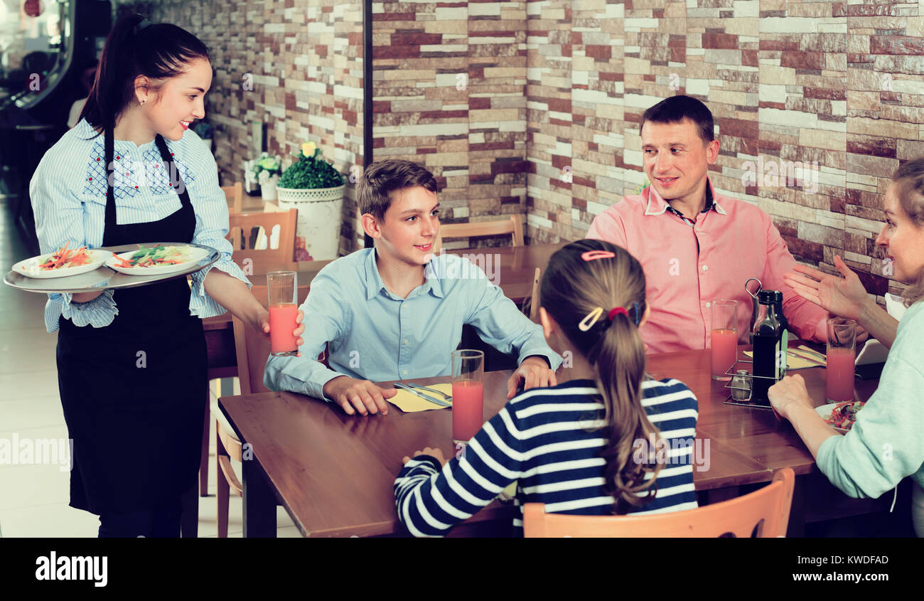 Young waitress serving cheerful family in comfy family cafe - Stock Image