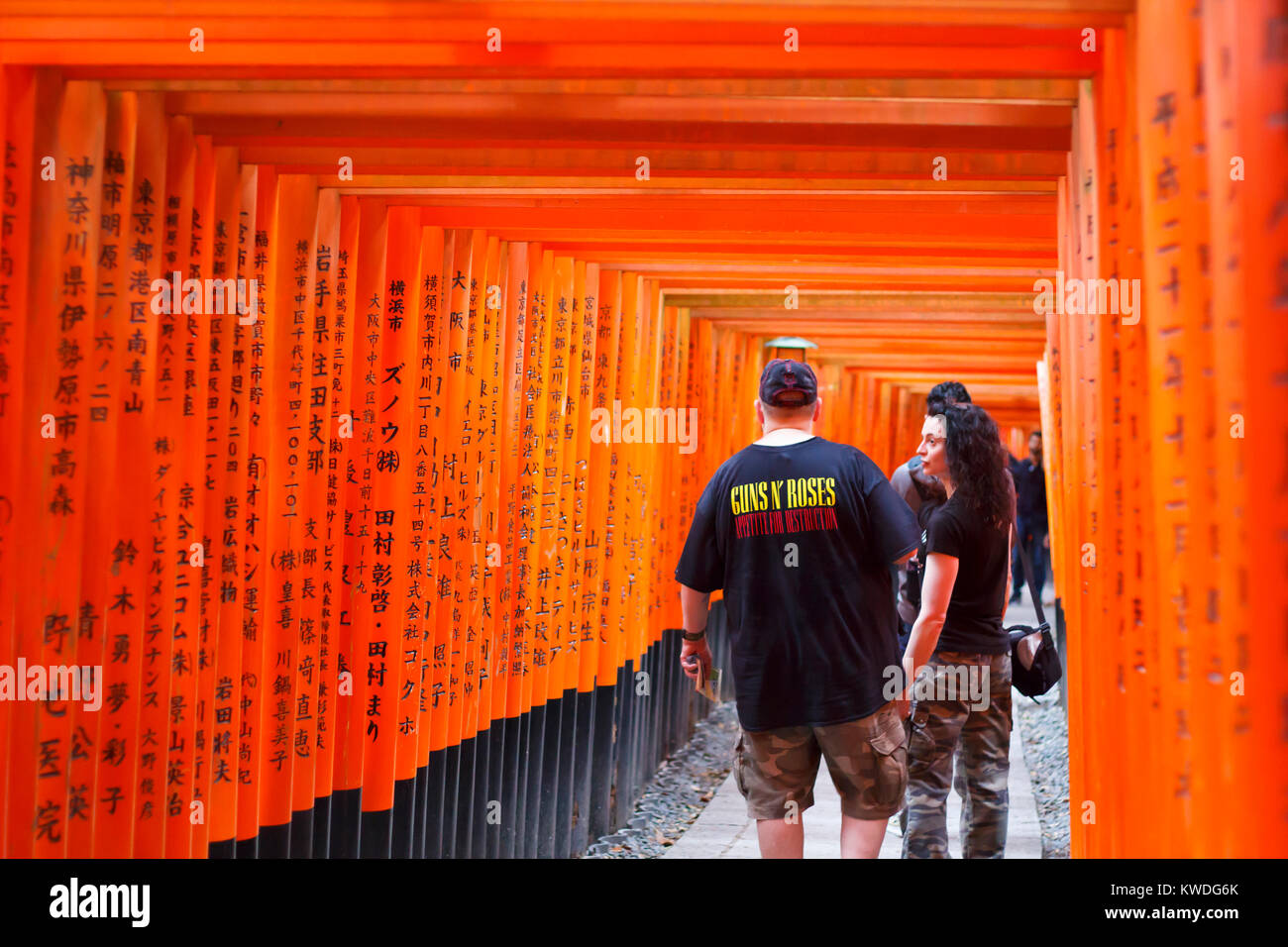 Tourists walking at the torii corridors in Fushimi Inari,  a path up to the mountain with many smaller shrines - Stock Image